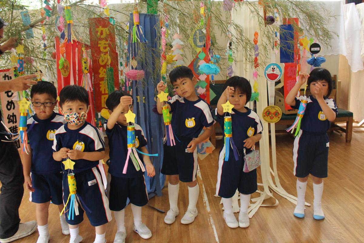 笹竹に七夕飾りをつける4才児