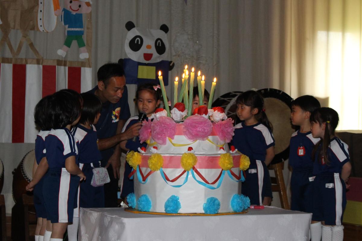 大きなバースデーケーキを囲む子どもたちの様子