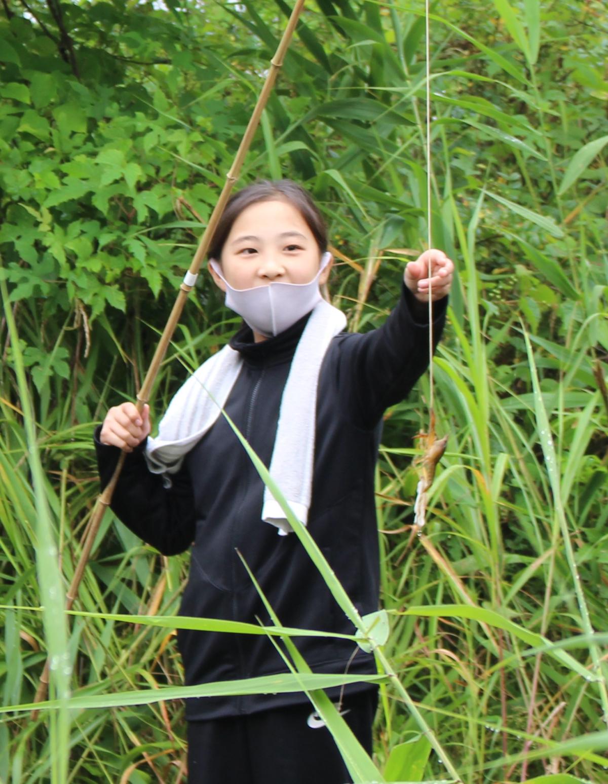 ザリガニが釣れて笑顔の小学生