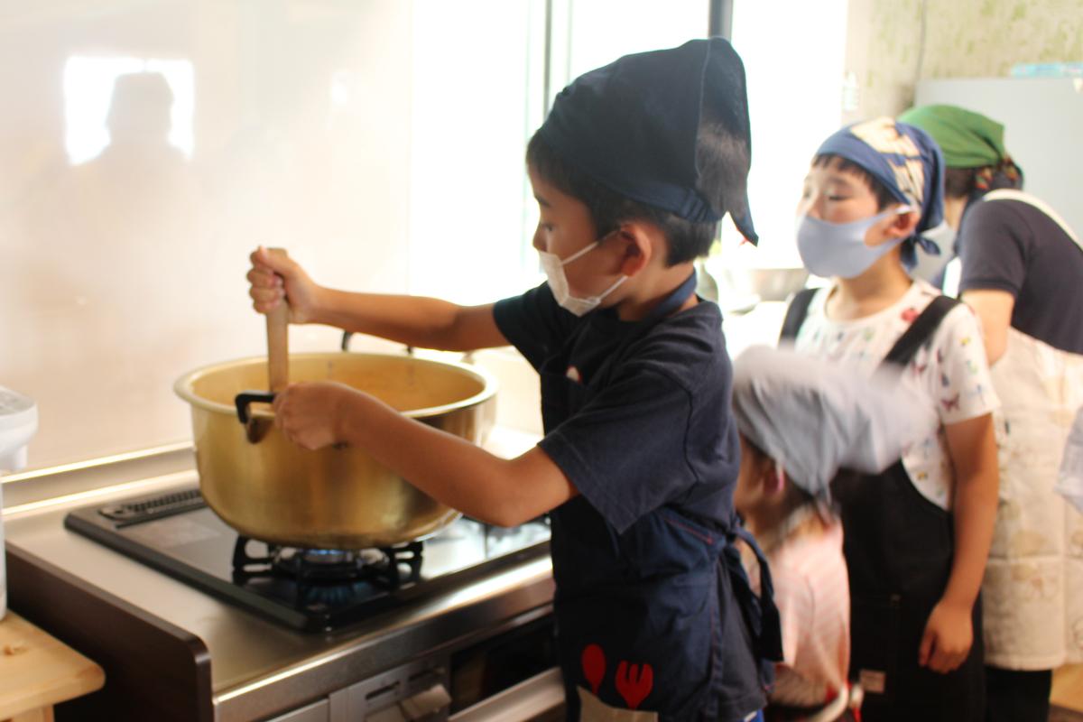 カレーライスの具材を炒める一年生