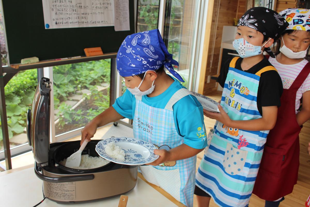 お皿にご飯を盛りつける小学生の様子