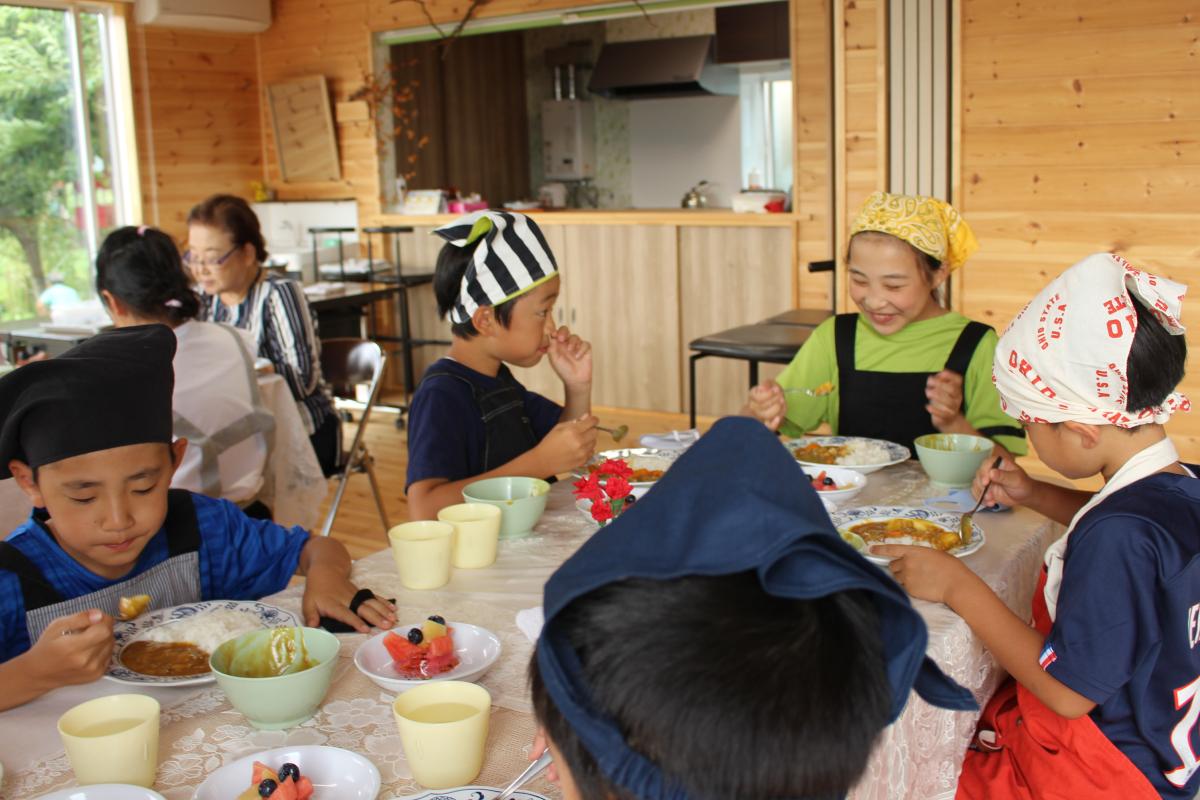 みんなでカレーライスを食べる小学生