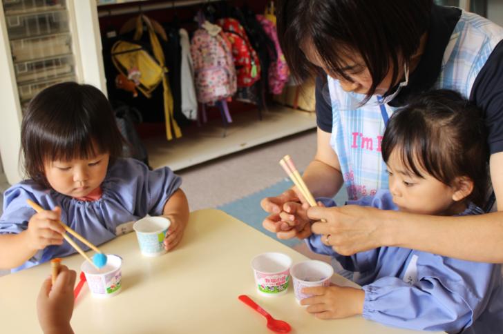 箸の練習に取り組む2才児