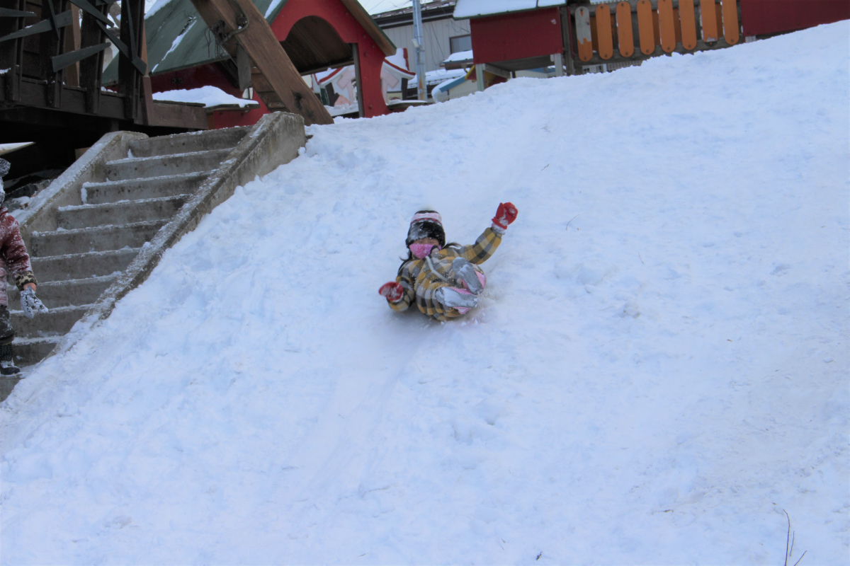 雪のダウンスロープを滑り下りる年少児