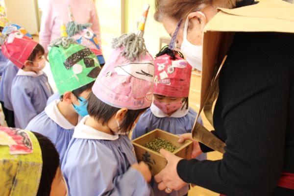 豆まきに使う炒った大豆を触る3才児