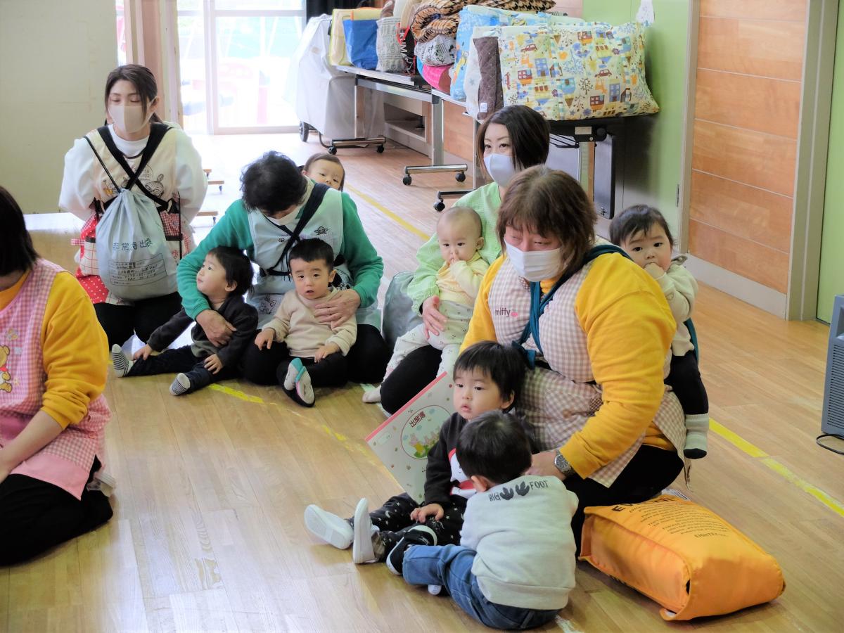避難訓練の集会に参加する0・1才児の様子