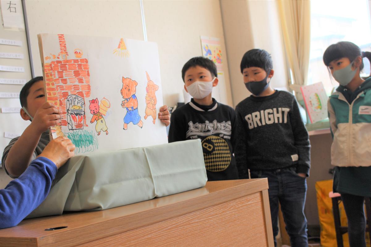 手作りの紙芝居を読み聞かせする学童の様子
