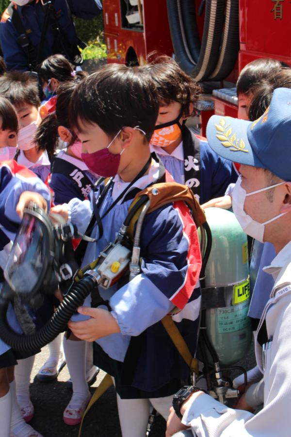 酸素ボンベ着用を体験する4才児の様子
