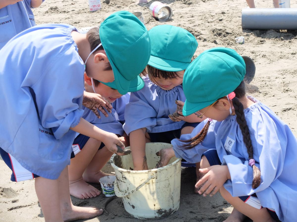 砂と海水を混ぜた泥で遊ぶ3才児