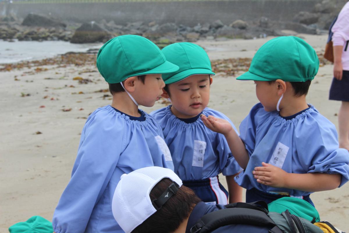 砂浜で何かを発見した3才児