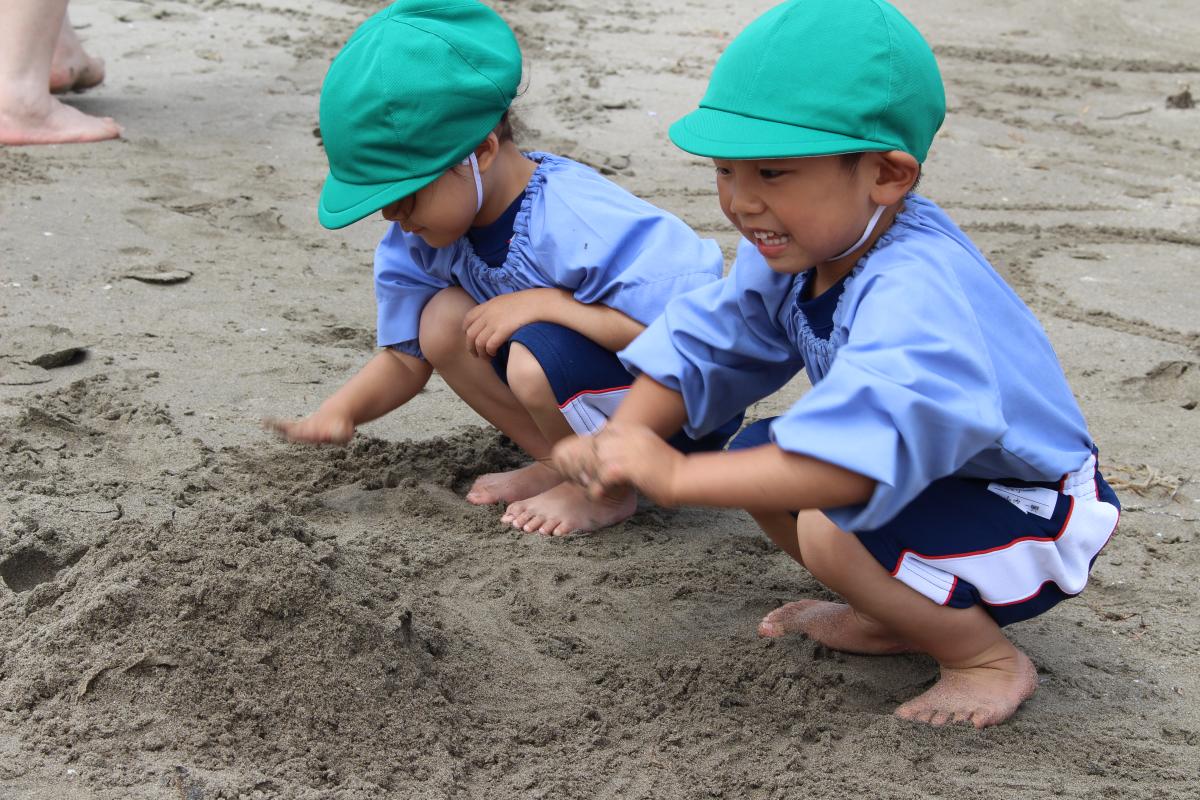 砂遊びを楽しむ3才児