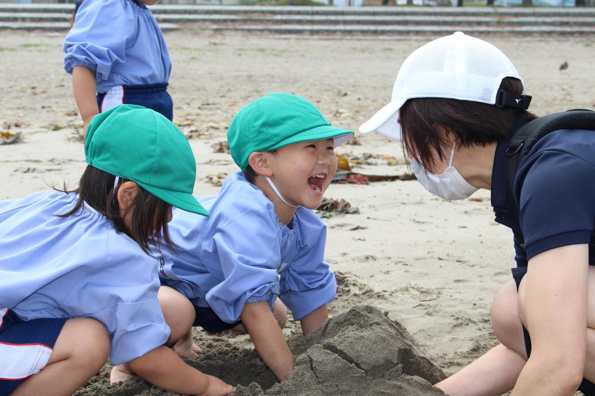 砂で作ったトンネルが開通して嬉しそうな3才児