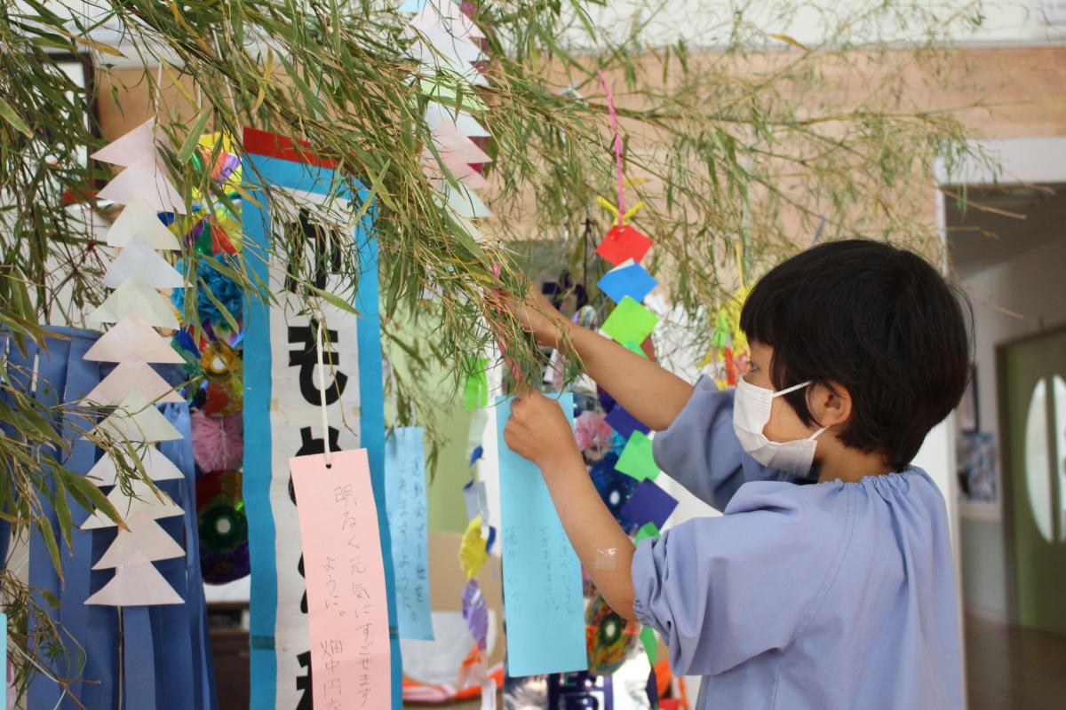 自分の短冊を笹竹に吊るす5才児の女の子