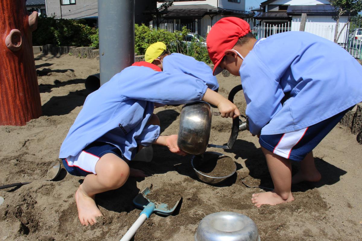 裸足になって砂場で遊ぶ4才児の様子