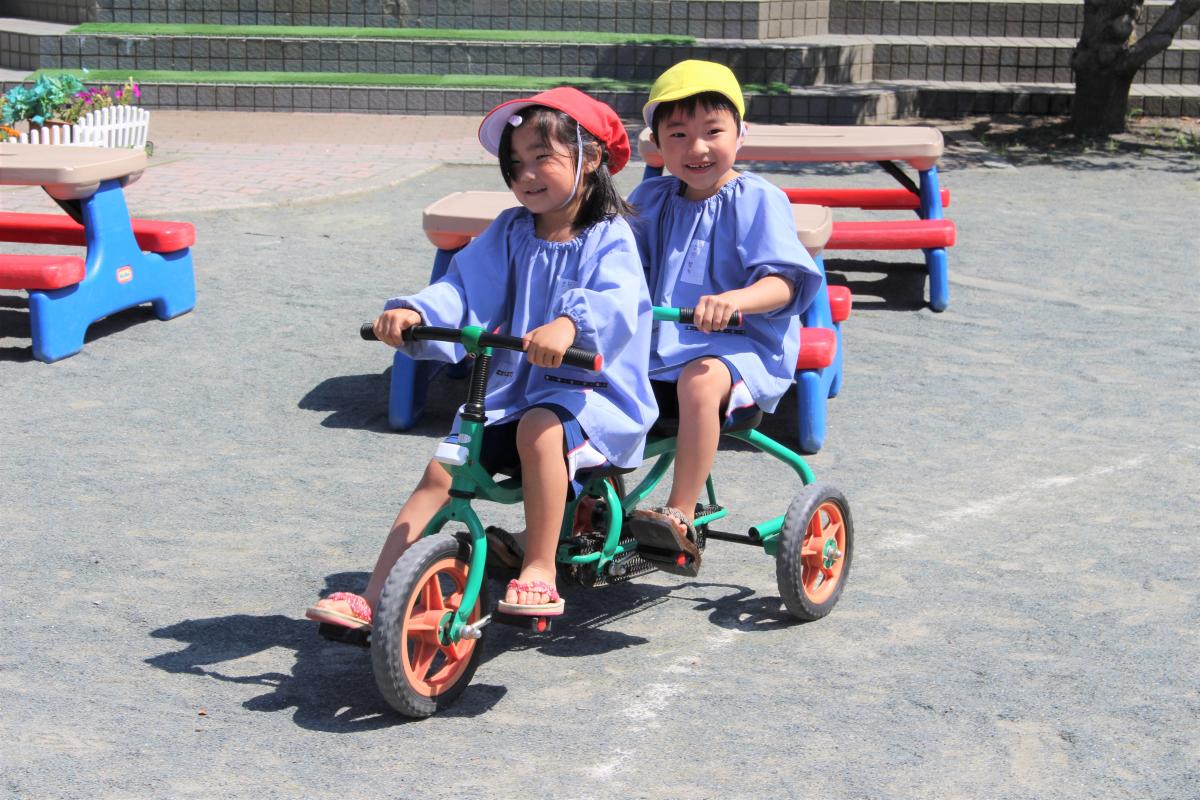 二人乗り三輪車で遊ぶ4才児と5才児