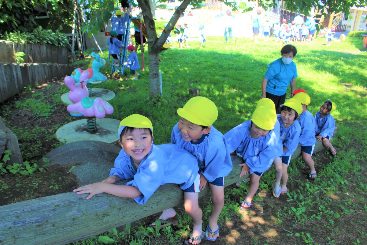 丸太に並んで座る5才児