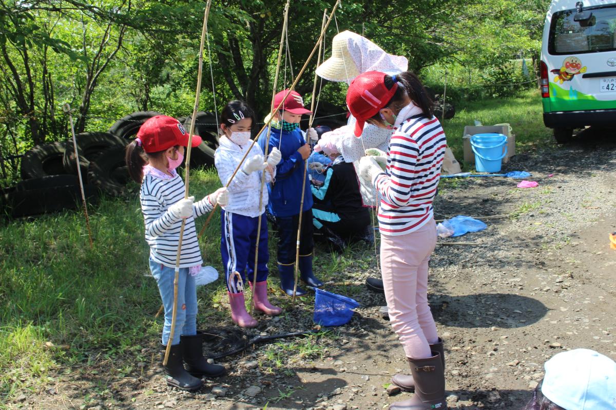 釣り竿にエサをつける小学生の様子