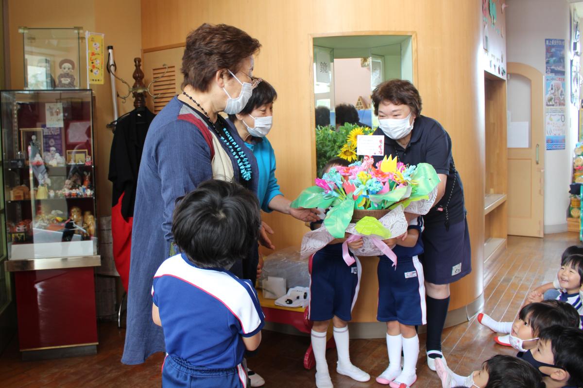 園長先生に手作りのお花をプレゼントする園児の様子