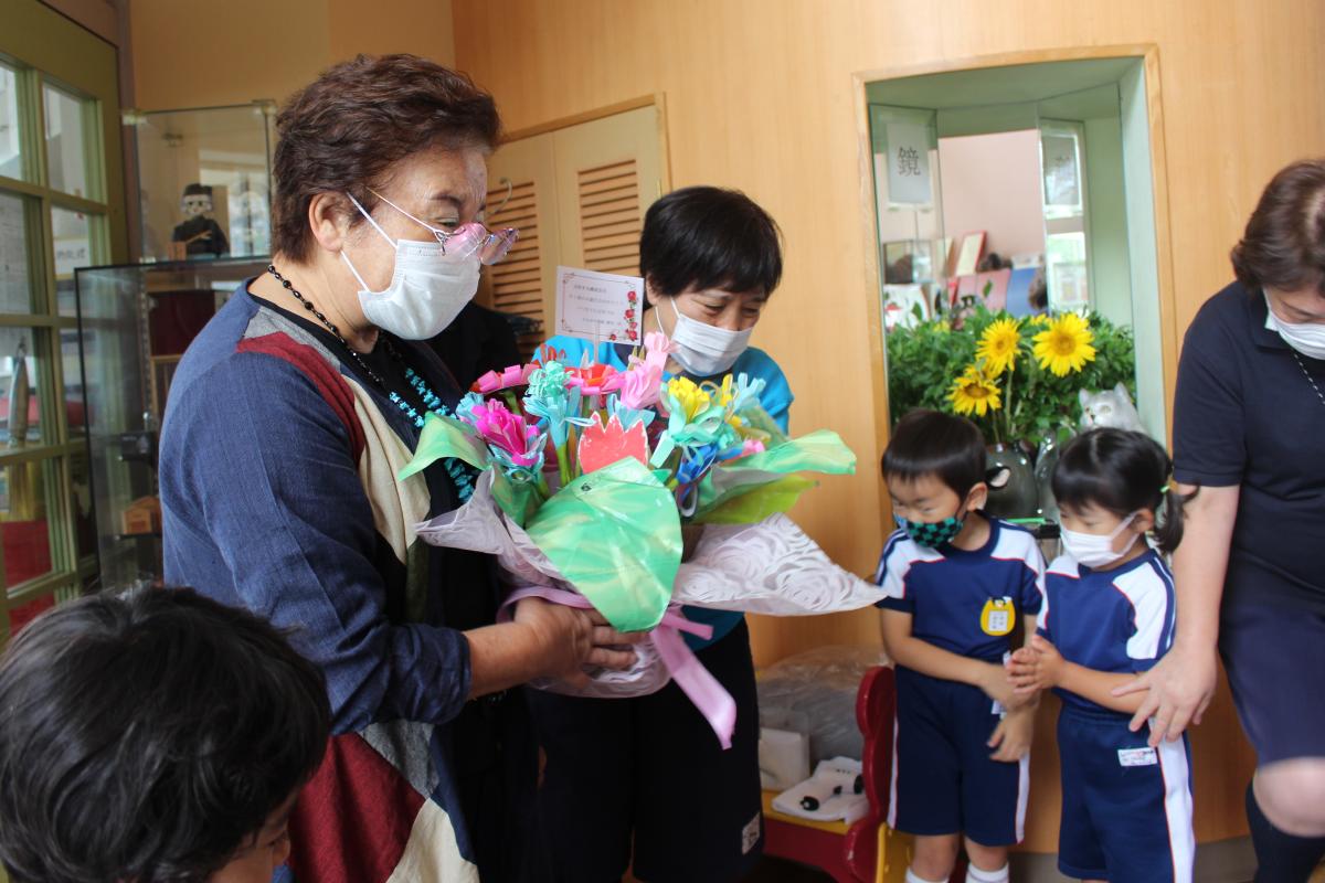 園児からもらった手作りのお花を持つ園長先生