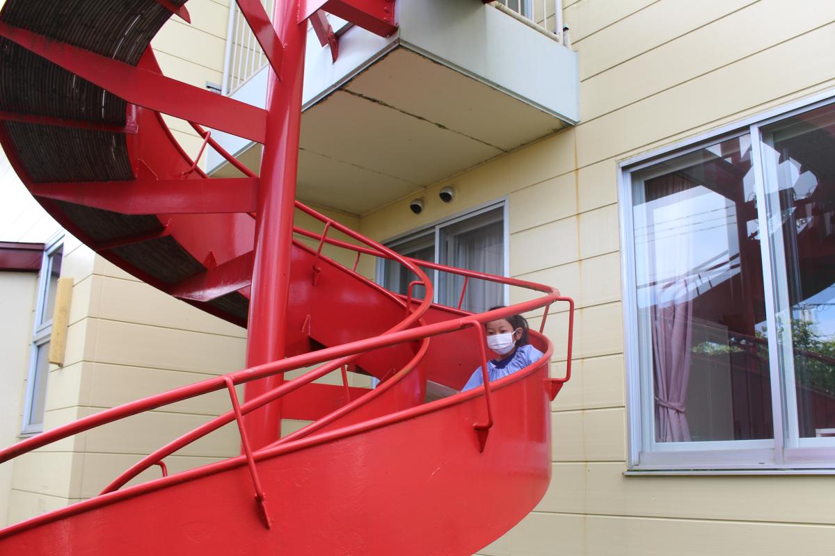 非常用の回転すべり台を体験する5才児の様子