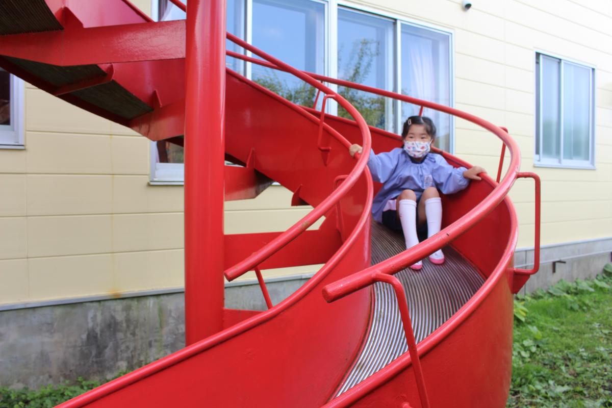 非常用の回転すべり台を体験する4才児の様子