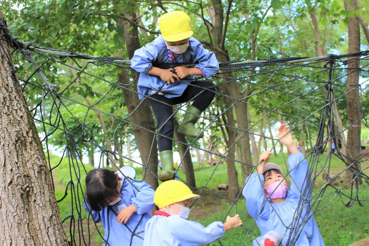 網をよじ登る5才児の女の子